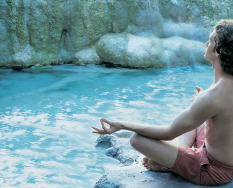 Man Meditating Near a Waterfall